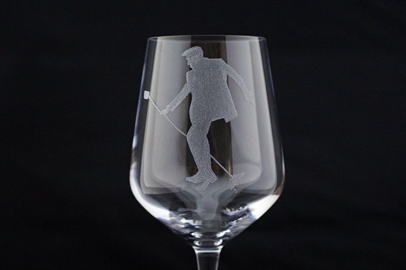 Close up of a wine glass hand engraved with Elvis doing his trade mark pose with a mic stand