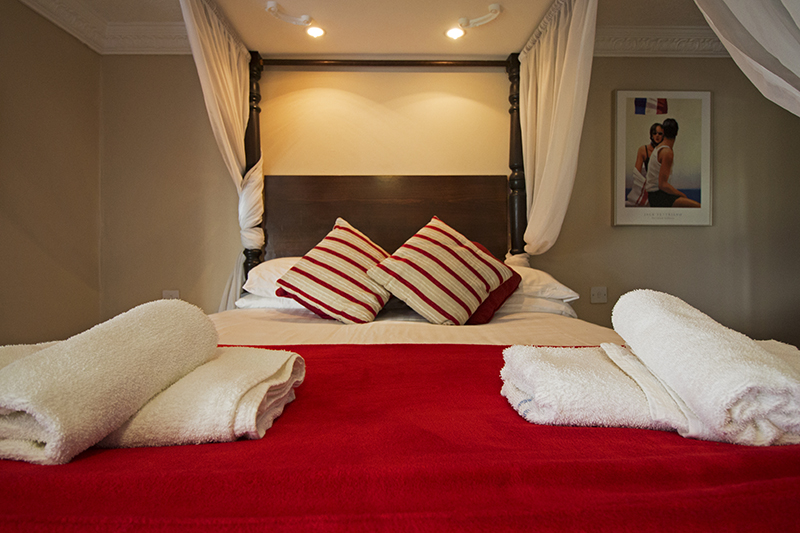 Lovely red wooden four poster bed with fluffy white towels