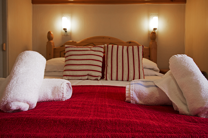 Fluffy white towels on a red bed spread ready for a stay at the lovely hotel