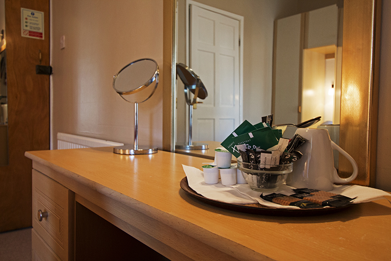 Tea, coffee and sugar with a kettle and biscuits ready to use at the vanity area