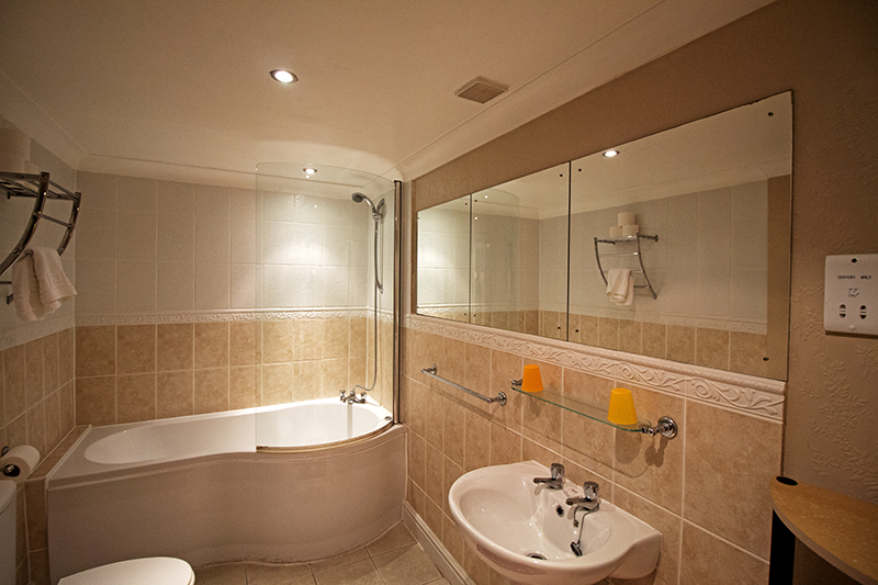 Large beautiful bathroom, with large corner bath and whole wall mirror