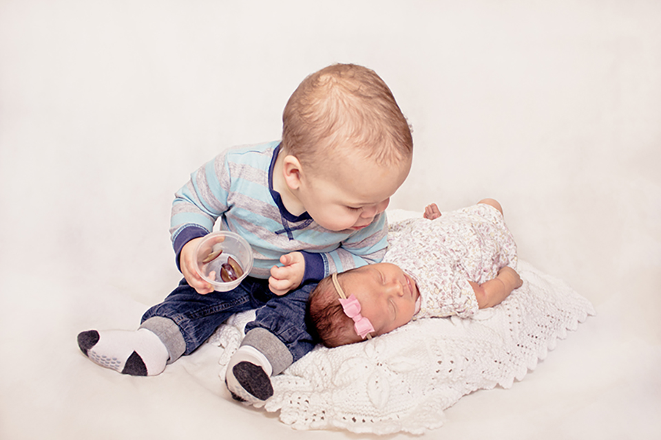 Big brother giving his baby sister a kiss on the head.