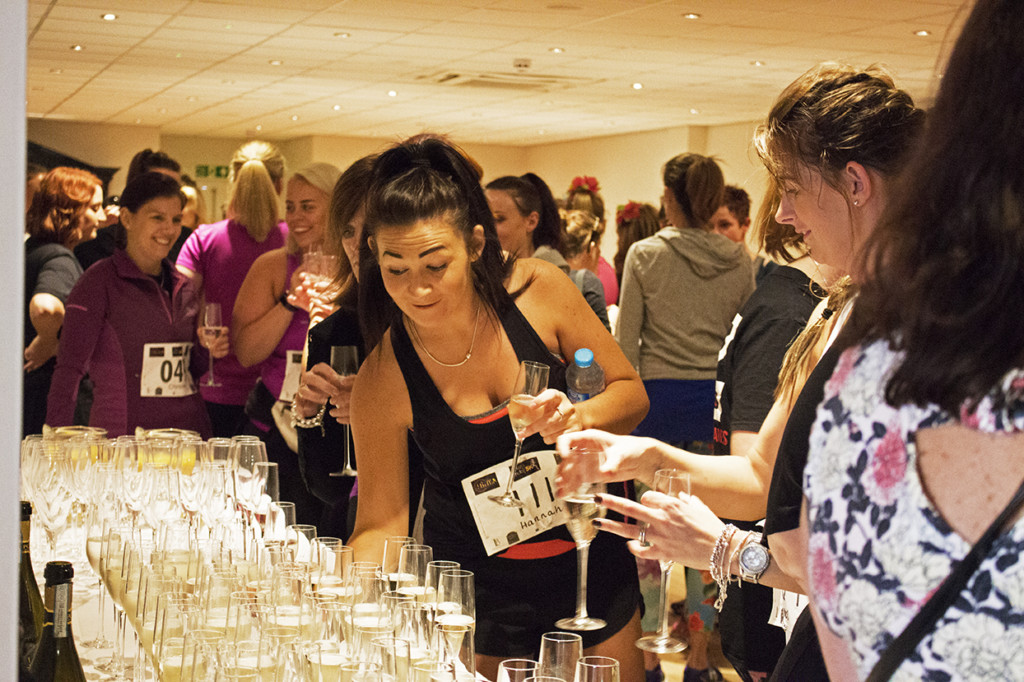 The first lot of women grabbing their drink of prosecco before the start of the run.