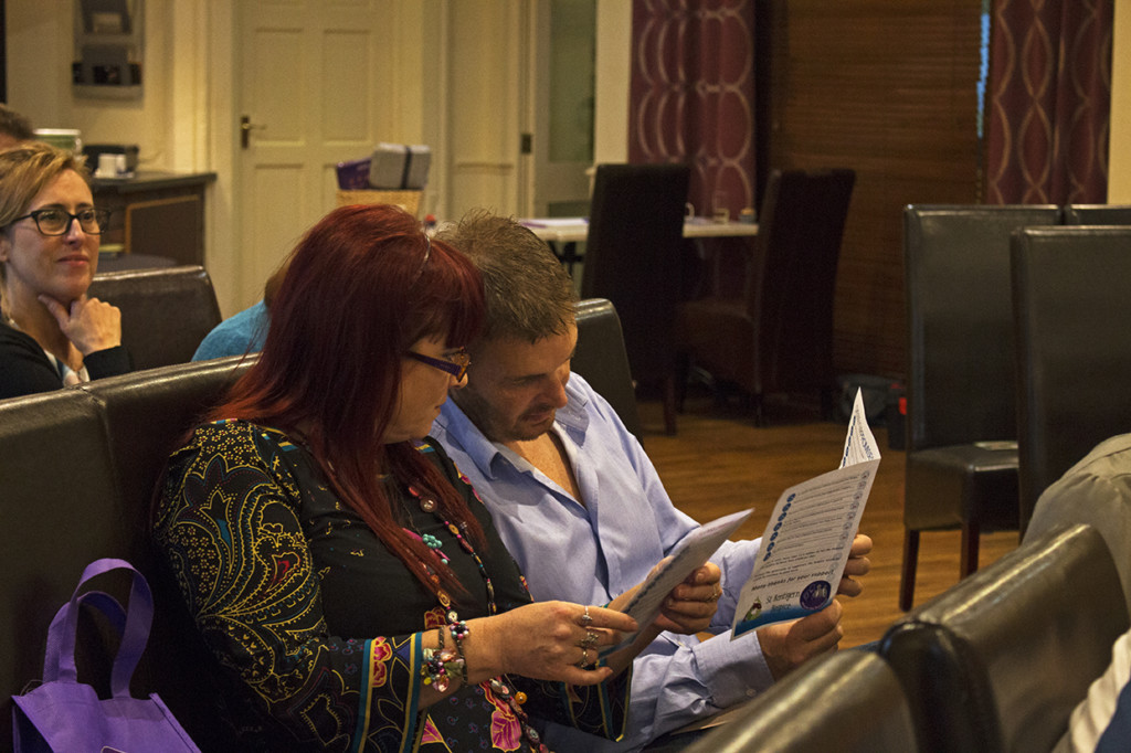 Two of the attendees looking through the itinerary so they don't miss the lots they want to bid on.