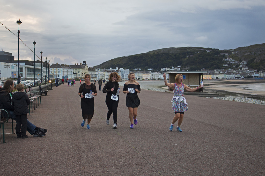 The group of women running in dress coming to the finish line.