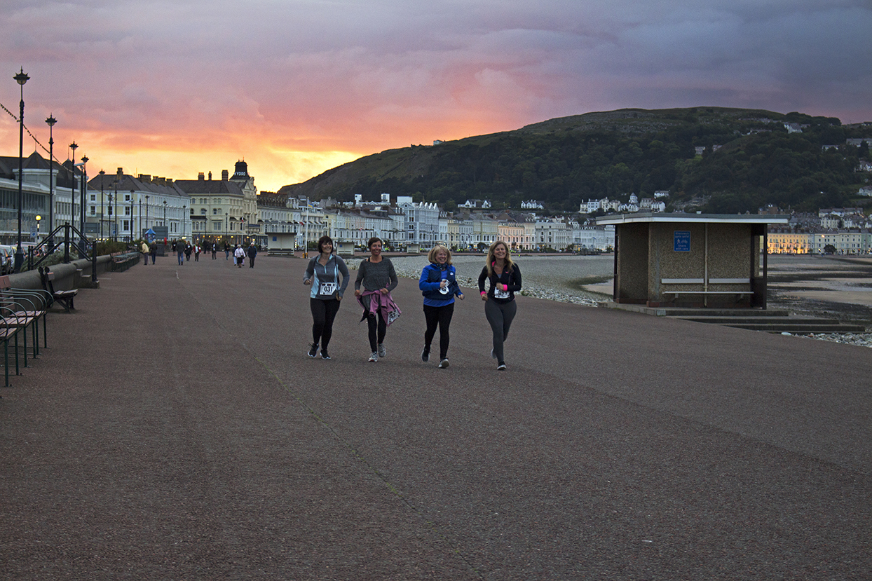 The sun is setting in the distance and the final runners are nearly home.